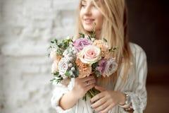 Ung caucasian kvinna för närbild som rymmer buketten av blommor, blickar till och med fönster med lyckligt leende på framsidan so royaltyfri bild