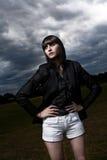 Ung caucasian kvinna i en park med den stormiga skyen Arkivfoton