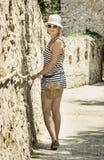 Ung caucasian kvinna i sjömandräkten som poserar vid den gamla väggen Royaltyfria Foton