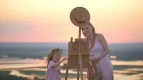 Ung caucasian kvinna med dottermålningnaturen på sommarkullen på solnedgången stock video