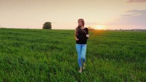 Ung Caucasian kvinna som går på en grön äng på solnedgången Hon är fundersam, omfamnar sig med henne händer långsamt arkivfilmer