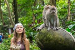 Ung Caucasian kvinna som poserar för ett foto med den gulliga apan på skuldra Den nyfikna macaquen att närma sig handelsresandefl arkivbild
