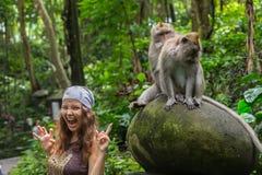 Ung Caucasian kvinna som poserar för ett foto med den gulliga apan på skuldra Den nyfikna macaquen att närma sig handelsresandefl royaltyfri foto