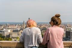 Ung caucasian kvinna som två lutar över stenräcket för att koppla av och se stadssikten av den Budapest Ungern royaltyfri foto