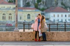 Ung caucasian kvinna två med shoppingpåsar vid en stålräcke i den Budapest Ungern som tar en selfie royaltyfri bild
