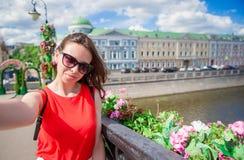Ung caucasian kvinnadanandeselfie på dragningsbakgrund utomhus Den lyckliga flickan tycker om hennes helg i europeisk stad royaltyfria foton