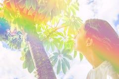 Ung caucasian kvinnaflicka med långt håranseende under trädet som ser upp i den gröna lövverket för himmel Begrundandelugn royaltyfria foton