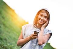 Ung caucasian kvinnlig jogger med hörlurar som lyssnar en musik arkivbild