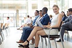 Ung Caucasian kvinnlig ledare som använder bärbara datorn i konferensrum som ler till kameran fotografering för bildbyråer