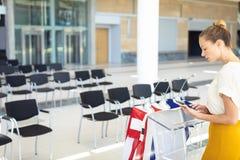 Ung Caucasian kvinnlig ledare som ser den digitala minnestavlan i tomt konferensrum fotografering för bildbyråer