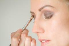 Ung caucasian kvinnlig modell på en makeup Applicera smink till a royaltyfria foton
