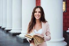 Ung caucasian kvinnlig student med böcker på universitetsområde Royaltyfria Bilder