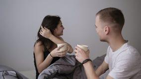Ung caucasian man i den vita T-skjortan att komma med kaffe i säng till hans älskade kvinna Lycka som känner sig bra romantisk mo stock video