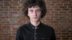 Ung caucasian man med lockigt hår som ser kameran, bakgrund för tegelstenvägg, allvarligt uttryck lager videofilmer