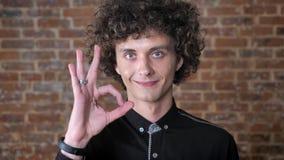 Ung caucasian man med lockigt hår som visar det acceptabla tecknet och ser kameran, bakgrund för tegelstenvägg lager videofilmer
