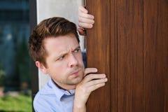 Ung caucasian man med torgskräck som ut spionerar och ser dörren royaltyfri fotografi