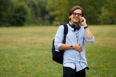 Ung Caucasian man som använder den utomhus- telefonen arkivfoto