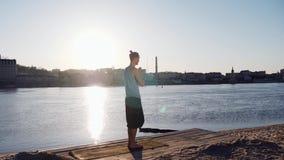 Ung caucasian man som kopplar av vid praktiserande yogakonditionövning på den near lugna floden för strand med staden på bakgrund stock video