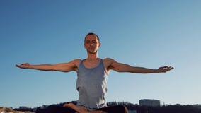 Ung caucasian man som kopplar av vid praktiserande yogakonditionövning på den near lugna floden för strand med staden på bakgrund lager videofilmer
