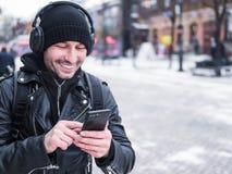 Ung Caucasian man som lyssnar till musik på hörlurar, medan walkin vid vinterstaden Royaltyfri Bild