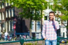 Ung caucasian man som talar vid mobiltelefonen på Arkivfoton
