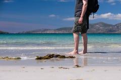 Ung caucasian man som tar en gå på en vit sandig strand med turkosvatten på hans semester Arkivbilder