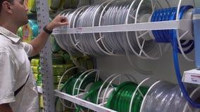 Ung caucasian man som väljer arbeta i trädgården slangen på lagret Shoppa för hushållutrustning stock video