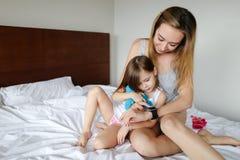 Ung caucasian moder som använder smart wathc och ligger på säng med den lilla dottern royaltyfri bild