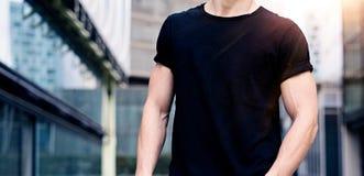 Ung caucasian muskulös man som bär den svarta tshirten och jeans som poserar på gatan av den moderna staden suddighet bakgrund arkivbilder