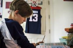 Ung caucasian pojke som gör läxa arkivfoton