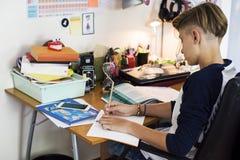 Ung caucasian pojke som gör läxa arkivfoto