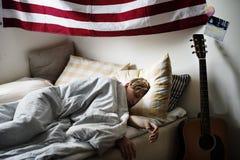 Ung caucasian pojke som sover i säng royaltyfri fotografi