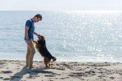 Ung caucasian pojke som spelar med hunden på stranden Man och hund som har gyckel på sjösidan royaltyfri fotografi