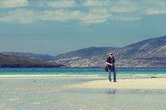 Ung Caucassian kvinna på en vit sandig strand i Luskentyre, ö av Harris, Skottland royaltyfria bilder