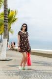 Ung caucausian brunett med sommarpåsen som strosar på strandpromenad Fotografering för Bildbyråer