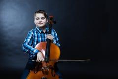 Ung cellist som spelar klassisk musik på violoncellen Arkivfoto