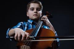 Ung cellist som spelar klassisk musik på violoncellen Fotografering för Bildbyråer