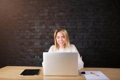 Ung charmig kvinnafreelancer som arbetar i internet på bärbar datordatoren som sitter i modern inre fotografering för bildbyråer