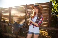 Ung cowgirl för glad rödhårig man som förbereder sadeln för ridninghäst Royaltyfria Bilder