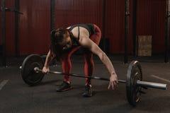 Ung crossfitkvinna som förbereder skivstången för lyftande vikt på idrottshallen arkivfoton