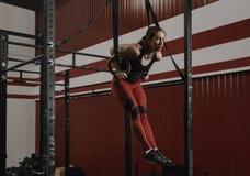 Ung crossfitkvinna som gör muskel-UPS på gymnastiska cirklar på idrottshallen fotografering för bildbyråer
