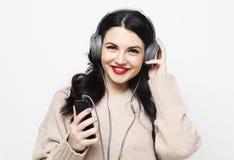 Ung curvy brunettkvinna i h?rlurar som lyssnar till musik arkivfoton