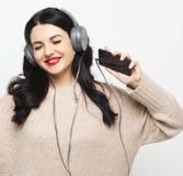 Ung curvy brunettkvinna i h?rlurar som lyssnar till musik royaltyfri foto