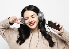 Ung curvy brunettkvinna i h?rlurar som lyssnar till musik arkivfoto