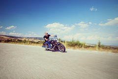 Ung cyklist som rider en motorcykel på en öppen väg Royaltyfri Foto