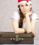 Ung dam i den Santa Claus hatten och gammal resväska Arkivfoto