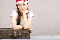 Ung dam i den Santa Claus hatten och gammal resväska Arkivbilder