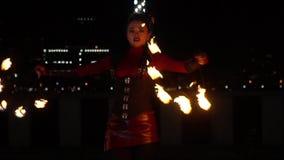 Ung dam i dräkten som utför en brandshow med fans som tänds på brand lager videofilmer