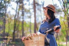Ung dam i en hatt, i en parkera med hennes tappningcykel Arkivfoto