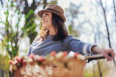Ung dam i en hatt, i en parkera med hennes tappningcykel Arkivbilder
